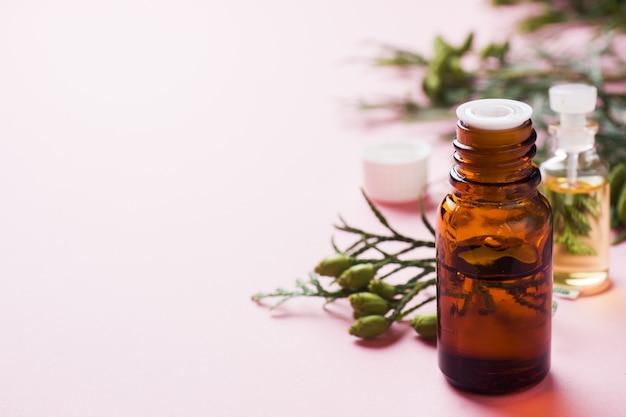 Thuja aroma etherische olie in een glazen pot op een roze oppervlak