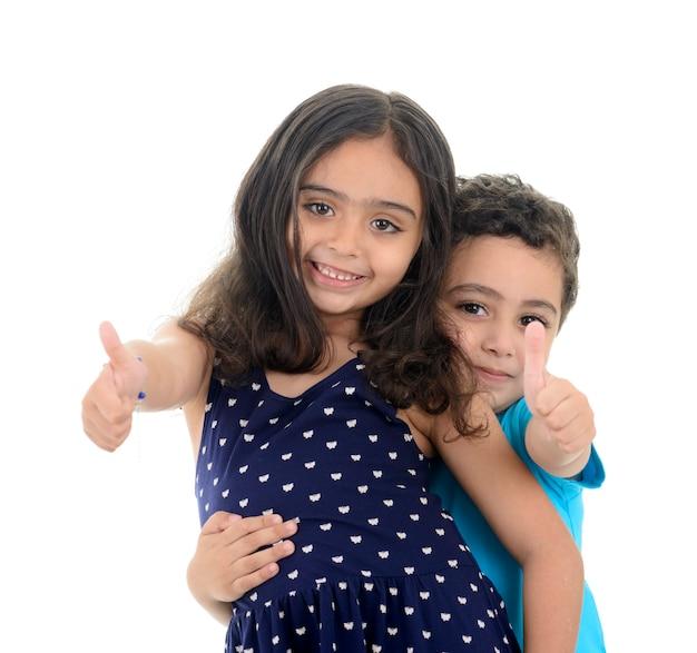 Thumbs up gelukkige jongen en meisje op witte achtergrond