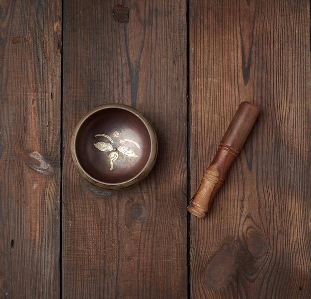 Tibetaanse koperen kom en houten stok op een tafel met bruine planken