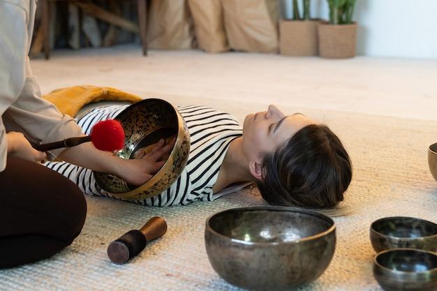 Tibetaanse medicijnvrouw gebruikt tibet-geluidstherapie en klankschalenmassage thuis tijdens meditatie