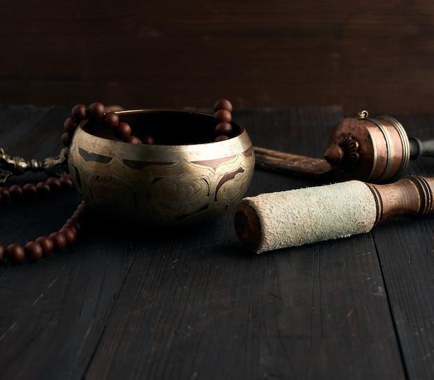 Tibetaanse zingende koperen kom met een houten klep op een bruine woo