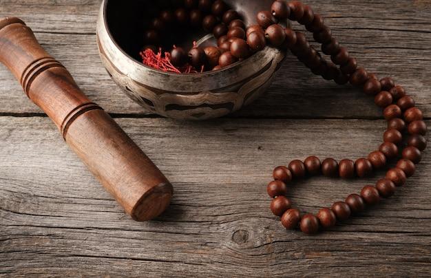 Tibetaanse zingende koperen kom met een houten klepel en gebedsrozenkrans