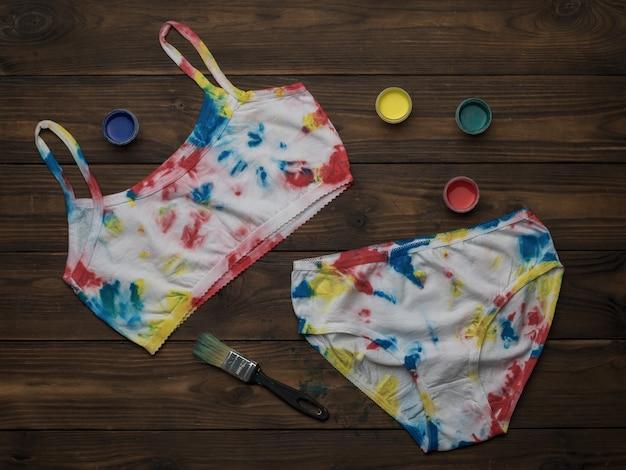 Tie dye ondergoed op een donkere houten tafel. gekleurd ondergoed in huis.