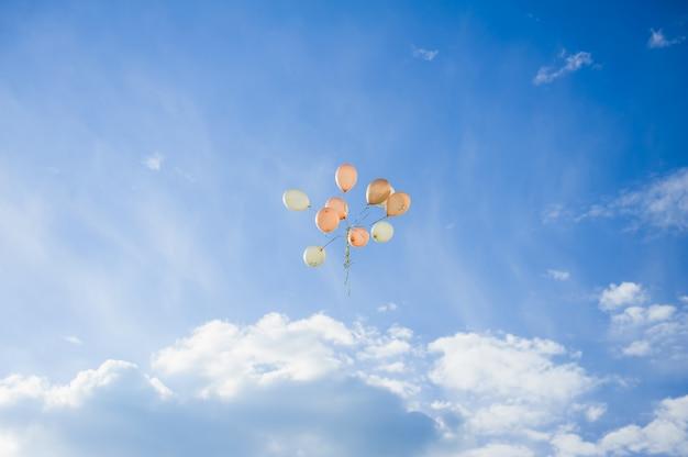 Tien ballonnen perzik kleur vliegen in de blauwe lucht