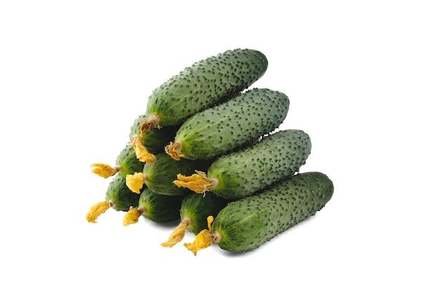 Tien groene komkommers met gedroogde gele bloemen zijn gestapeld in een gelijkmatige stapel in de vorm van een piramide en zijn geïsoleerd op een schone witte achtergrond met een lichte zachte schaduw.