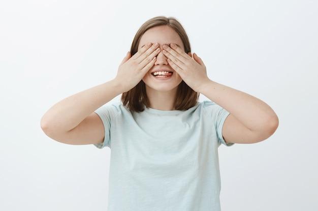 Tien tellen en je gaan zoeken. portret van speelse emotionele wachtende vrouw met handpalmen op ogen die vreugdevol glimlachen van opwinding terwijl vrienden een geheim cadeau over grijze muur brengen