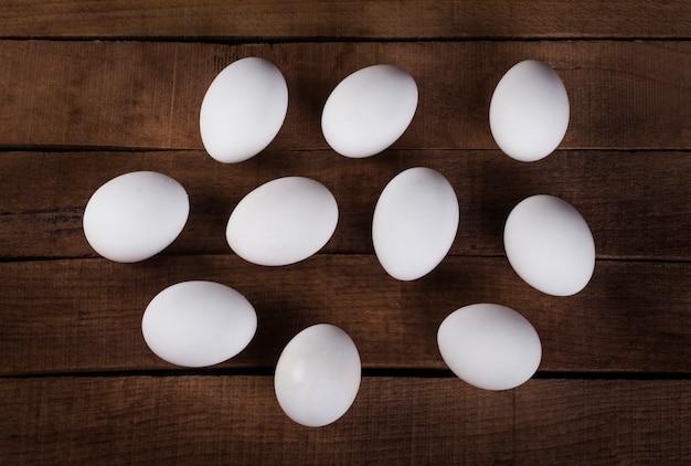 Tien witte eieren op een houten rustieke bovenaanzicht als achtergrond.