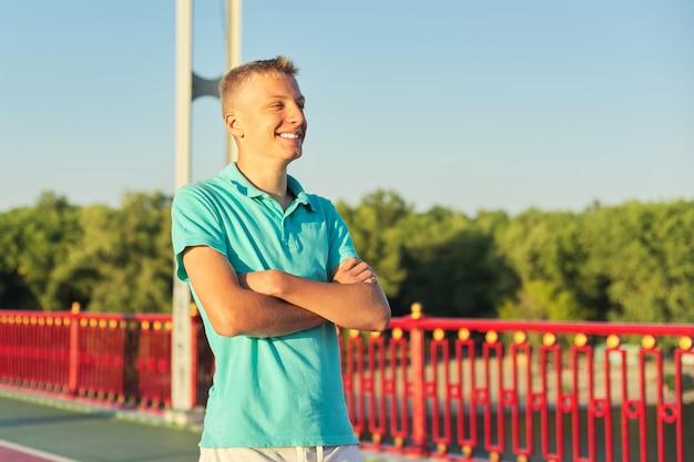 Tiener 15, 16 jaar oude blonde jongen poseren met gevouwen armen
