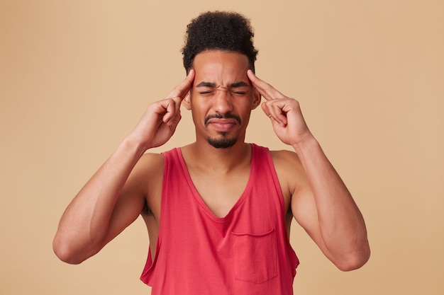 Tiener afro-amerikaanse man, ongelukkig uitziende man met afro kapsel en baard. het dragen van een rode tanktop. masseer tempels, bij pijn. voel hoofdpijn, moe over een pastelbeige muur