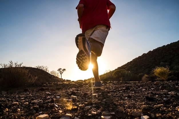 Tiener alleen rennen in de bergen bij de zonsondergang - sport en atletisch concept - positieve vibes
