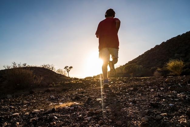 Tiener alleen rennen in de bergen met zijn koptelefoon bij de zonsondergang - sport en atletisch concept
