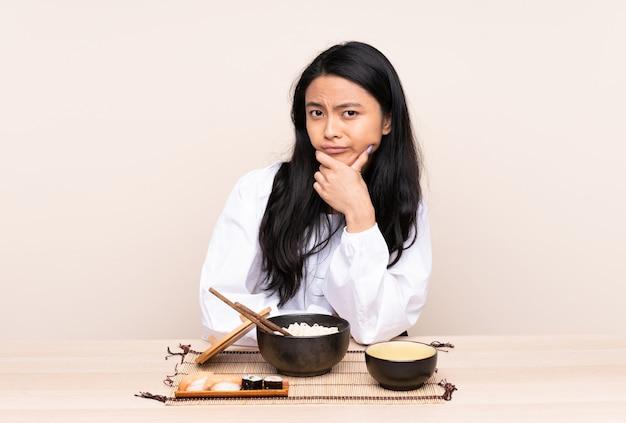 Tiener aziatisch meisje dat aziatisch voedsel eet dat bij beige het denken wordt geïsoleerd