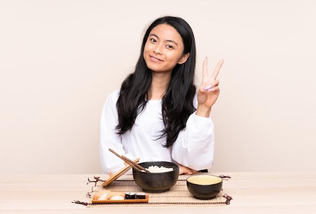Tiener aziatisch meisje dat aziatisch voedsel eet dat op beige en overwinningsteken glimlacht toont