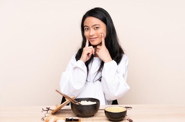 Tiener aziatisch meisje dat aziatisch voedsel eet dat op beige wordt geïsoleerd die met een gelukkige en prettige uitdrukking glimlacht