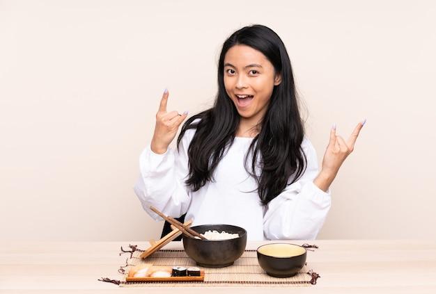 Tiener aziatisch meisje dat aziatisch voedsel eet dat op beige wordt geïsoleerd die rotsgebaar maakt