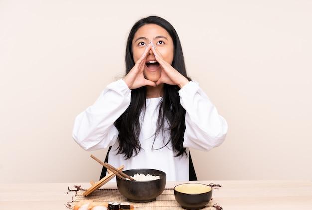 Tiener aziatisch meisje dat aziatisch voedsel op beige muur eet en iets schreeuwt aankondigt
