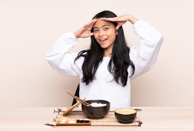 Tiener aziatisch meisje dat aziatisch voedsel op beige muur met verraste uitdrukking eet
