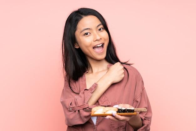 Tiener aziatisch meisje dat sushi eet die op roze achtergrond wordt geïsoleerd die een overwinning viert