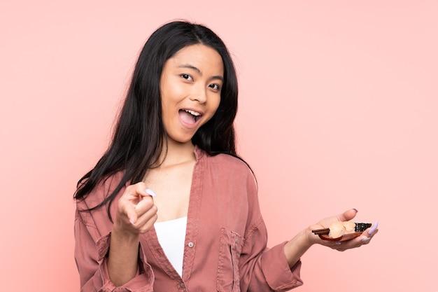 Tiener aziatisch meisje dat sushi eet die op roze puntenvinger naar jou wordt geïsoleerd