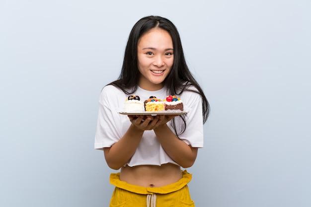Tiener aziatisch meisje dat veel verschillende minicakes houdt