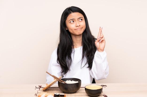 Tiener aziatisch meisje die aziatisch die voedsel eten op beige achtergrond met vingers wordt geïsoleerd die en het beste kruisen wensen