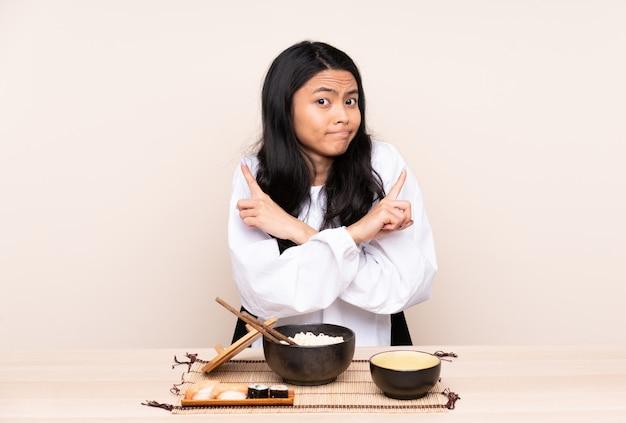 Tiener aziatisch meisje die aziatisch die voedsel eten op beige muur wordt geïsoleerd die aan de laterals richten die twijfels hebben