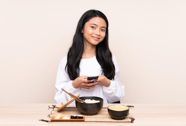 Tiener aziatisch meisje die aziatisch die voedsel eten op beige wordt geïsoleerd