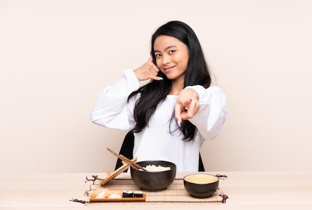 Tiener aziatisch meisje die aziatisch voedsel op beige muur eten die telefoongebaar maken en voorzijde richten