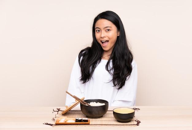 Tiener aziatisch meisje die aziatisch voedsel op beige muur met verraste gelaatsuitdrukking eten