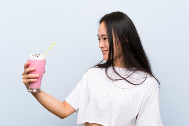 Tiener aziatisch meisje die een aardbeimilkshake met gelukkige uitdrukking houden