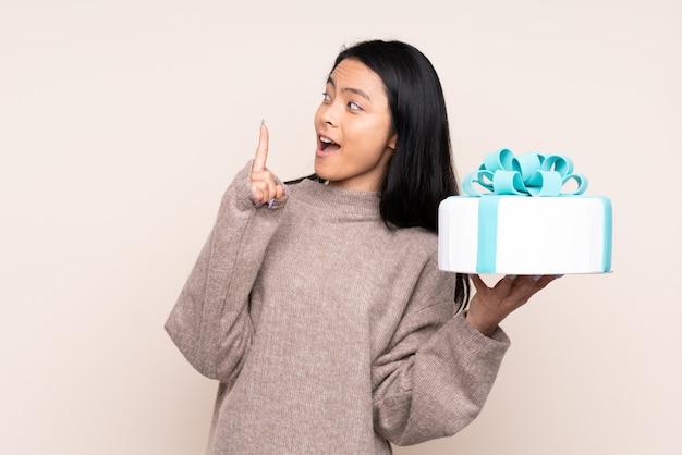 Tiener aziatisch meisje die een grote cake houden die op beige muur wordt geïsoleerd met de bedoeling de oplossing te realiseren terwijl het opheffen van een vinger