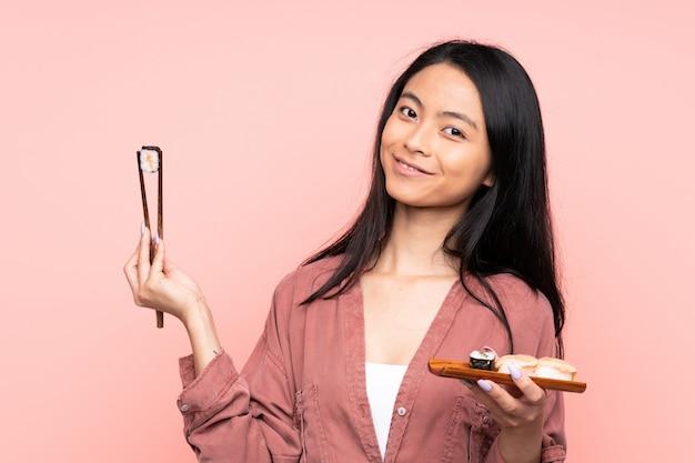 Tiener aziatisch meisje die sushi eten die op roze worden geïsoleerd