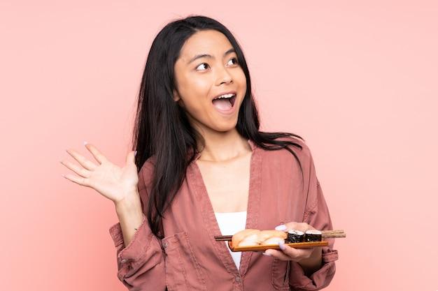 Tiener aziatisch meisje die sushi op roze muur met verrassingsgelaatsuitdrukking eten