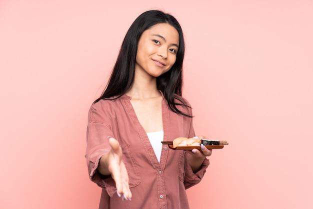 Tiener aziatisch meisje die sushi op roze muurhandenschudden eten na veel