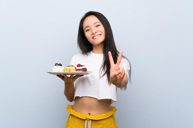 Tiener aziatisch meisje die veel verschillende minicakes houden die en overwinningsteken glimlachen tonen
