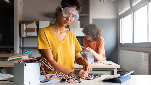 Tiener aziatisch meisje middelbare school student in de klas leren elektronica camera kijken. horizontale bannerafbeelding. ruimte kopiëren. onderwijsconcept.