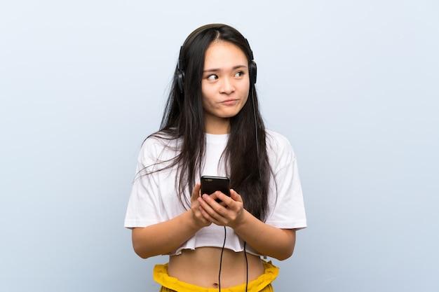 Tiener aziatische meisje het luisteren muziek over geïsoleerde blauwe muur