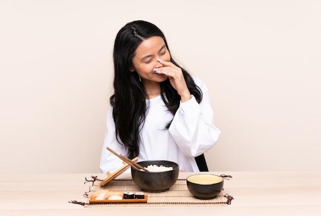 Tiener aziatische vrouw die aziatisch voedsel eet dat op beige achtergrond wordt geïsoleerd