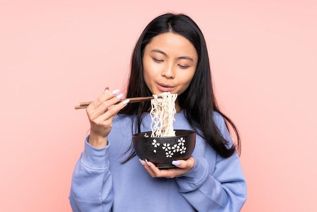 Tiener aziatische vrouw die op beige muur een kom noedels met eetstokjezand houden die het blazen omdat zij heet zijn