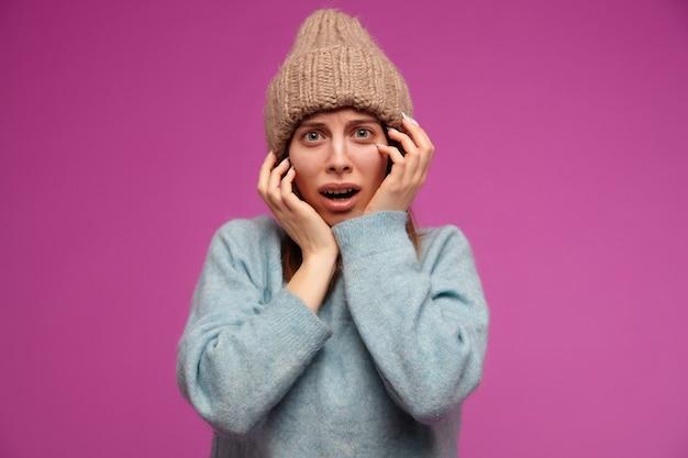 Tiener, bang uitziende vrouw met donkerbruin lang haar. het dragen van blauwe trui en gebreide muts. haar gezicht aanraken in angst over de paarse muur