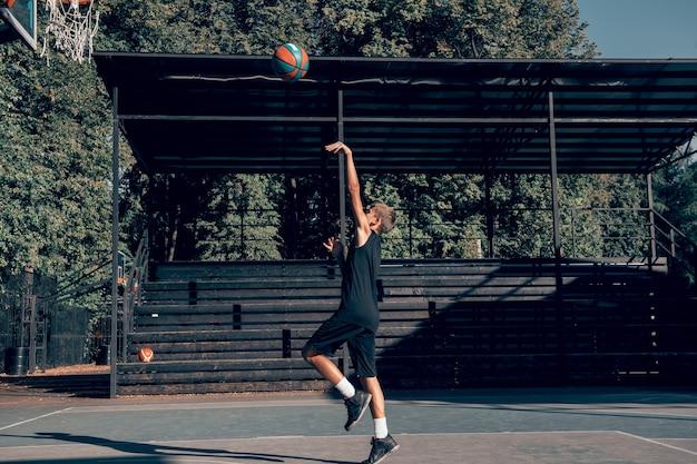Tiener basketbalspeler die alleen traint op sportveld bal gooien