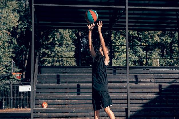 Tiener basketbalspeler die alleen traint op sportveld en bal naar hoepel gooit