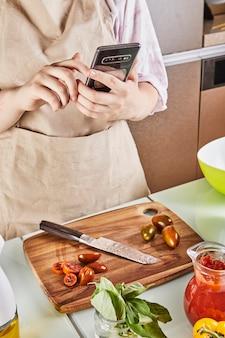 Tiener bereidt virtuele online leerboek-tutorial voor en bekijkt digitaal recept op mobiele telefoon met touchscreen terwijl hij thuis gezond voedsel in de keuken bereidt.