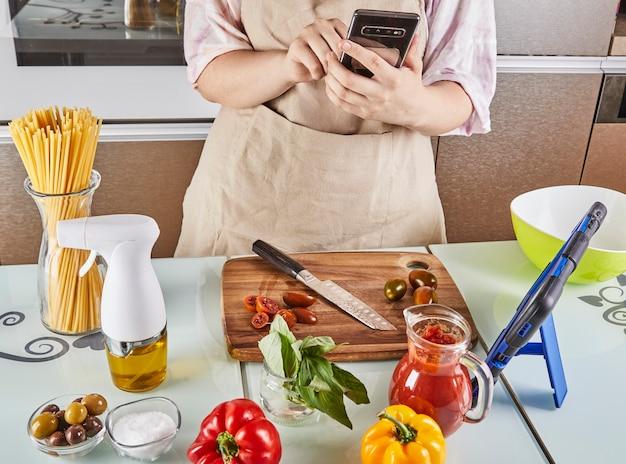Tiener bereidt virtuele online leerboektutorial voor en bekijkt digitaal recept op mobiele telefoon met touchscreen terwijl hij thuis gezond voedsel in de keuken bereidt