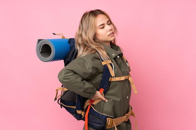 Tiener bergbeklimmer meisje met een grote rugzak geïsoleerd op roze die lijdt aan rugpijn omdat ze zich heeft ingespannen