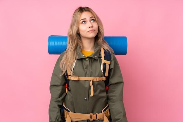 Tiener bergbeklimmer meisje met een grote rugzak geïsoleerd op roze en opzoeken