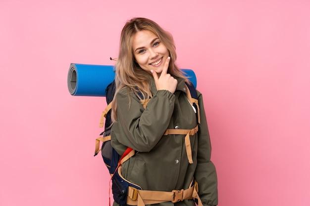 Tiener bergbeklimmer meisje met een grote rugzak geïsoleerd op roze glimlachen