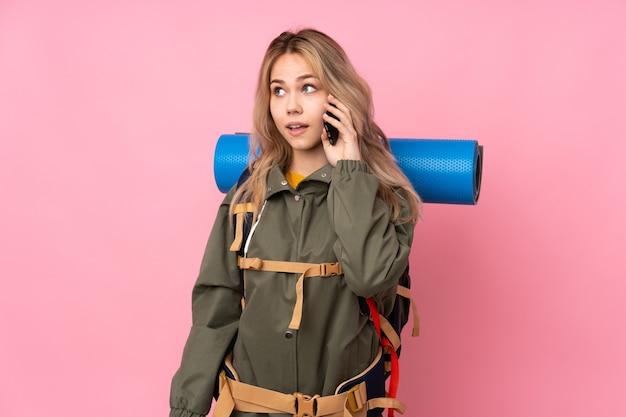 Tiener bergbeklimmer meisje met een grote rugzak geïsoleerd op roze houden een gesprek met de mobiele telefoon met iemand