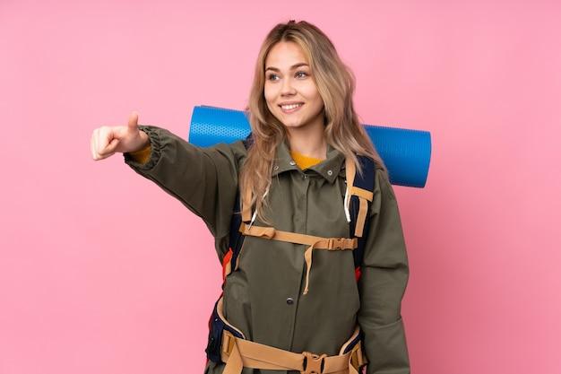 Tiener bergbeklimmer meisje met een grote rugzak geïsoleerd op roze met een duim omhoog gebaar