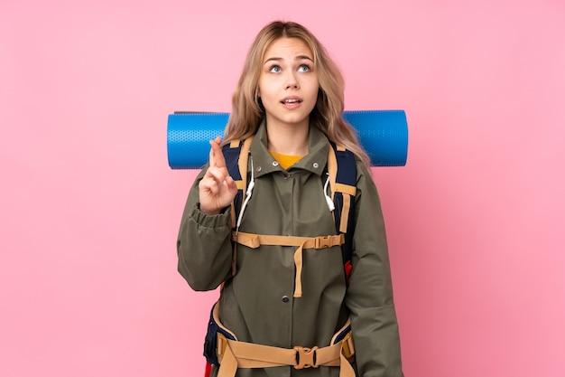 Tiener bergbeklimmer meisje met een grote rugzak geïsoleerd op roze met vingers kruisen en het beste wensen